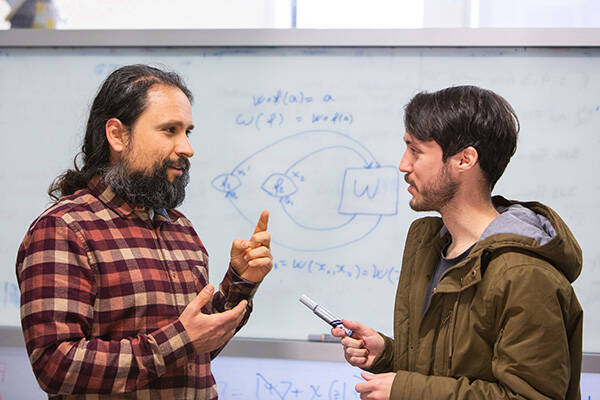 Dr Fabio Costa and Germain Tobar are standing in front of a whiteboard with mathematics written on it, mid-discussion.